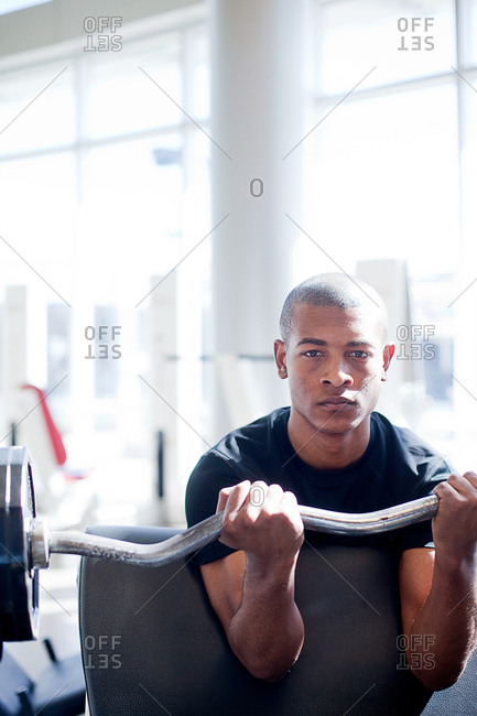 Portrait of determined young man lifting barbell in gym
