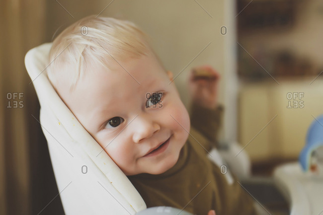 Close-up of cute boy looking away while sitting on high chair