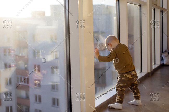 Full length of boy standing by window at home