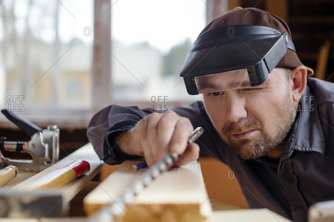 Carpenter wearing protective eyewear working at workbench in workshop