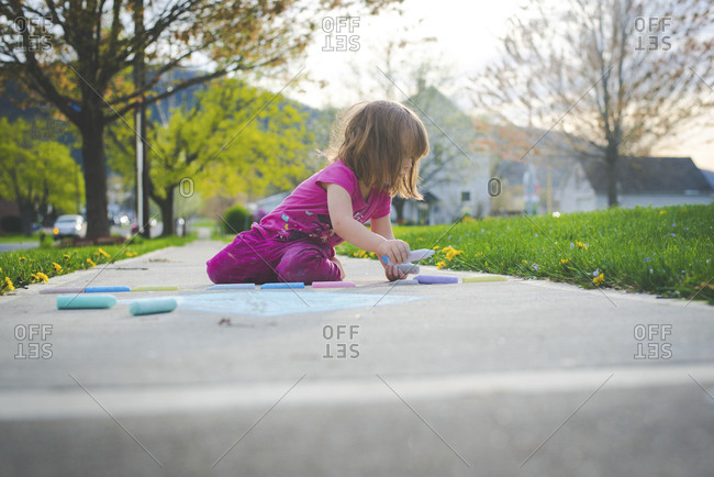 Girl drawing with chalks on footpath
