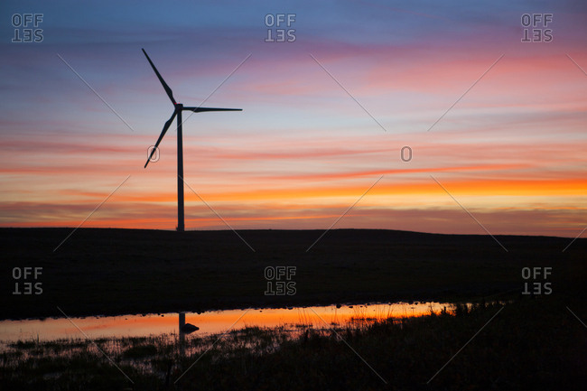 Silhouette windmill on field against cloudy sky during sunset