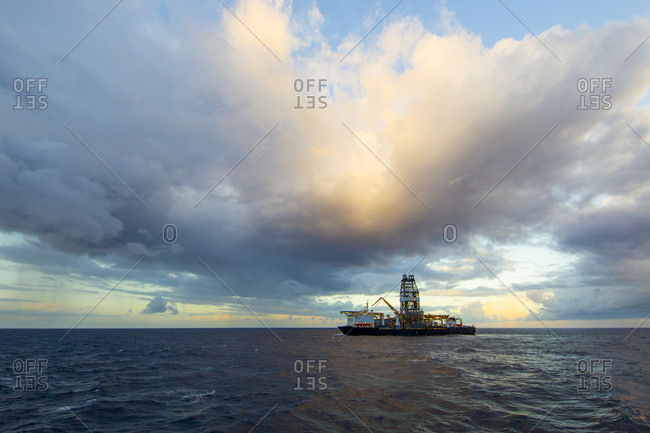 Drill ship in sea against cloudy sky