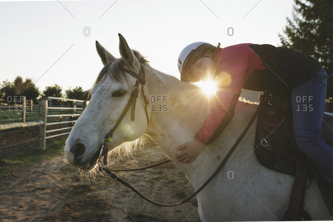 Side view of girl sleeping on horse at barn