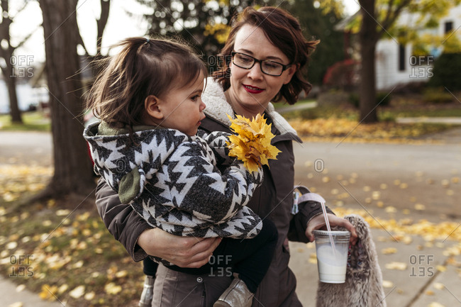 Mother carrying daughter while holding disposable glass at park