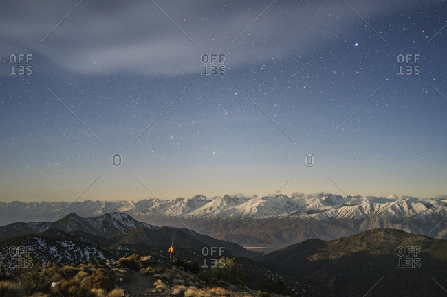 Distant view of hiker standing amidst mountains against star field sky