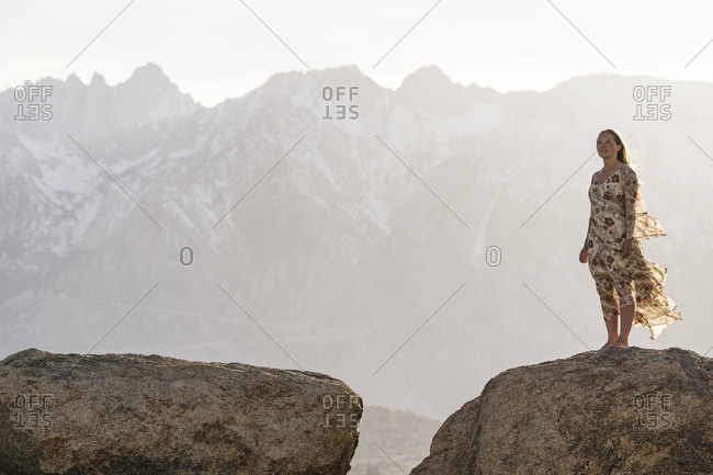 Young woman standing on rock against mountains during foggy weather