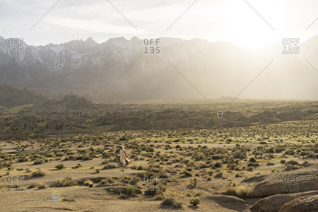 Distant view of young woman walking on field against mountains
