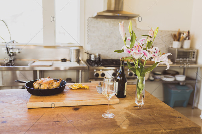Cooked chicken meat in cooking pan on cutting board with wineglass and vase at table