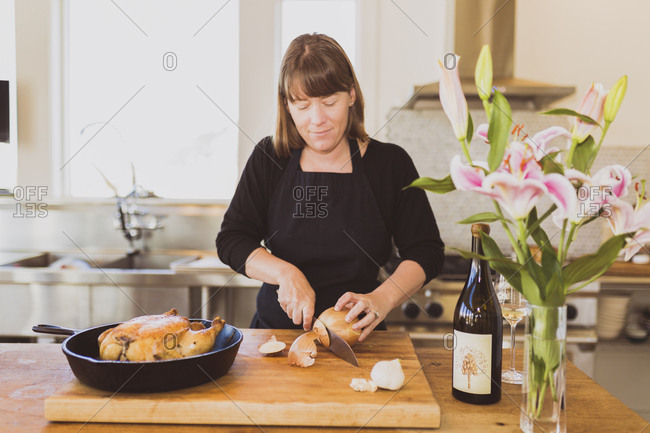 Woman cutting onion on cutting board at table