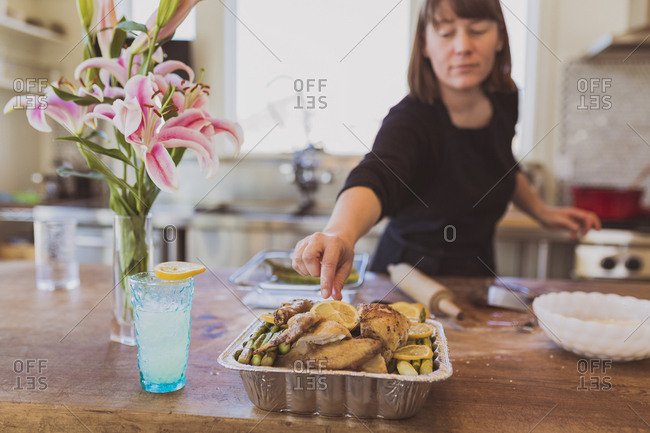 Woman reaching for lemon slice on chicken meat at table