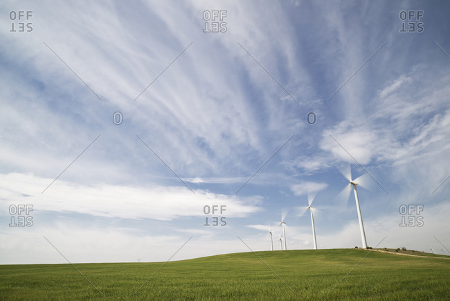 Wind turbines on field against cloudy sky