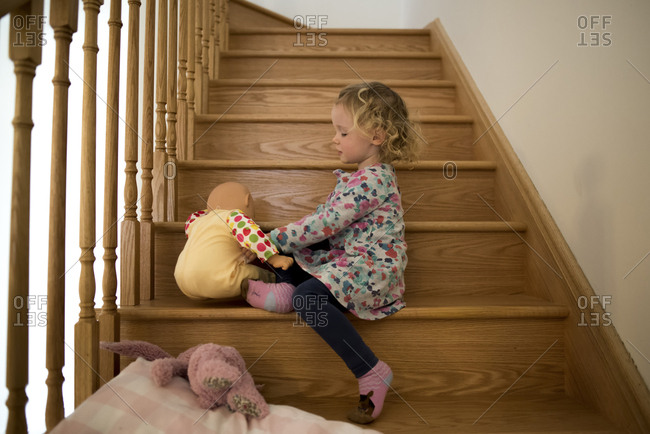 Side view of girl playing with doll while sitting on wooden steps at home