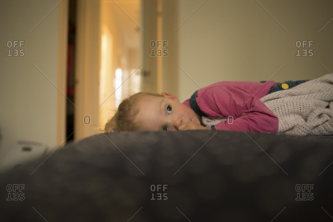 Side view of thoughtful girl looking away while lying in bed