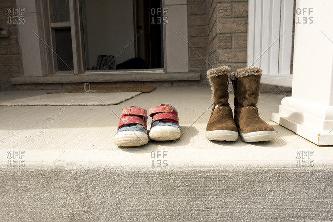 Pairs of shoes on retaining wall outside house