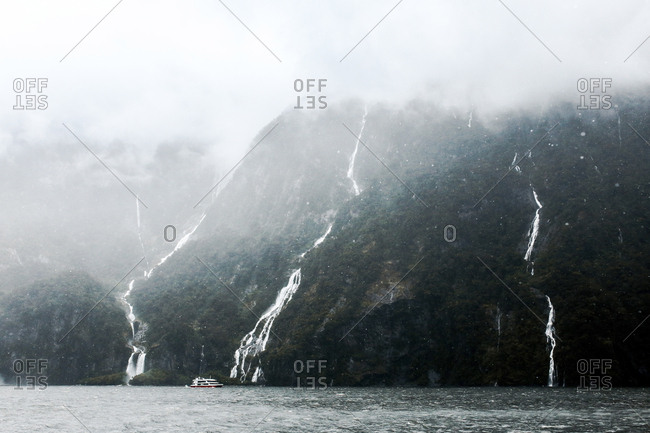 Scenic view of waterfalls at Milford sound during foggy weather
