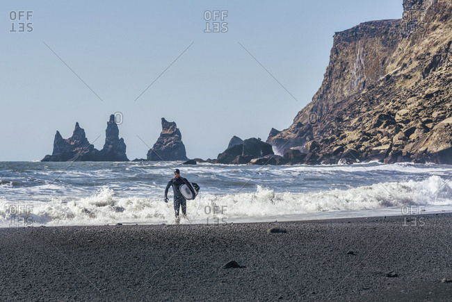 Man with surfboard walking at Black beach against clear sky during sunny day