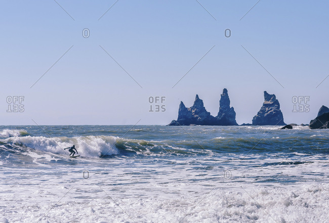 Man surfing on sea against clear sky during sunny day