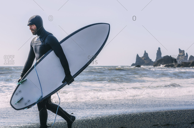 Man with surfboard walking at Black beach against clear sky