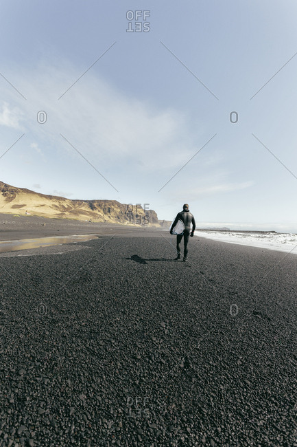 Rear view of man carrying surfboard while walking at Black beach against sky during sunny day