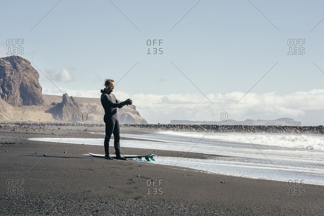 Man with surfboard standing at shore against sky during sunny day