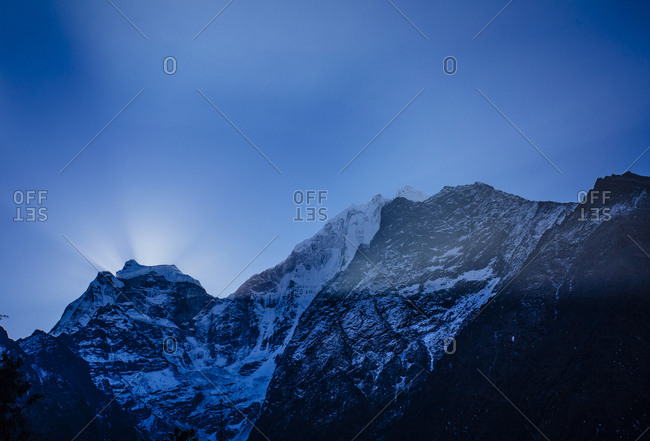 Low angle view of snowcapped mountains against blue sky at dusk
