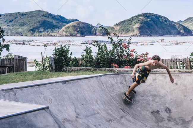 Shirtless young man skateboarding on sports ramp at park