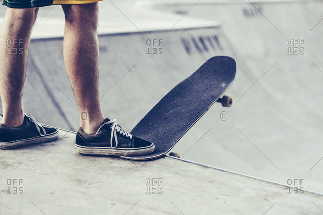 Low section of young man with skateboard at the edge of sports ramp