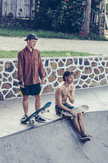 Young male friends resting with skateboards at the edge of concrete pool