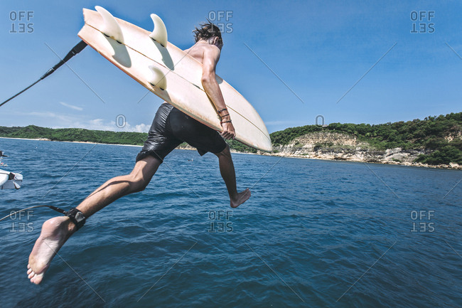 Man with surfboard jumping into sea against sky during sunny day