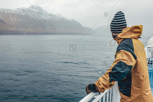 Side view of man looking at view while standing by railing on boat during rainy season