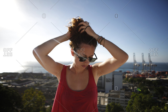Woman with hand in hair standing against sky