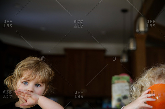 Thoughtful girl looking away while covering mouth with hands at home