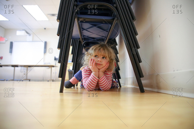 Thoughtful girl lying under stacked chairs on floor at home