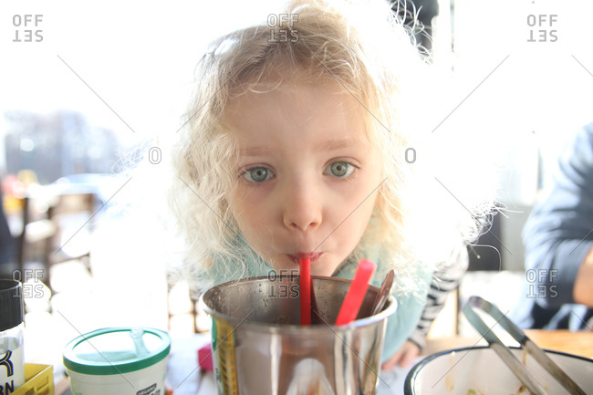 Close-up portrait of girl drinking from container at bright lit restaurant