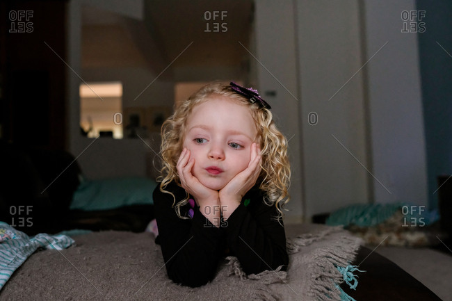 Thoughtful girl lying with head in hands on bed at home