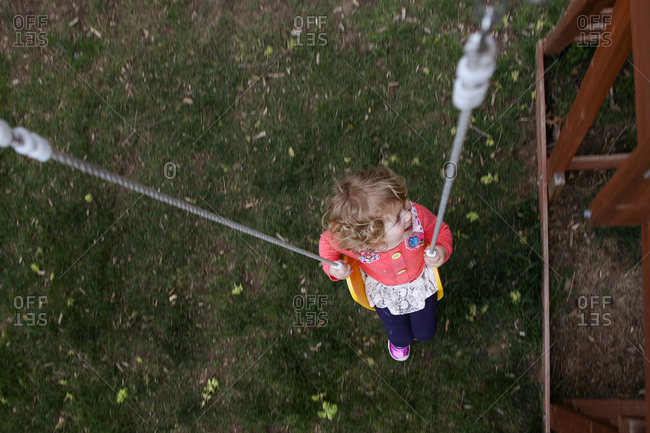 High angle view of girl swinging at yard