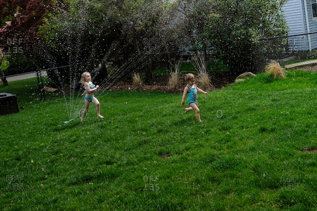 Girls playing in spraying water at lawn