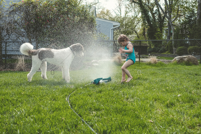 Side view of girl and dog standing by spraying water at yard