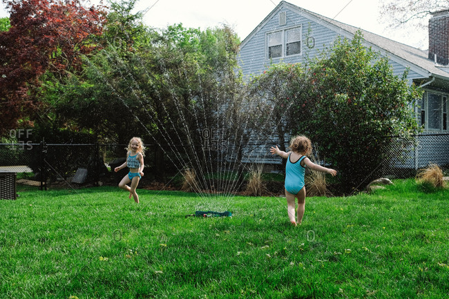 Girls playing with spraying water at lawn