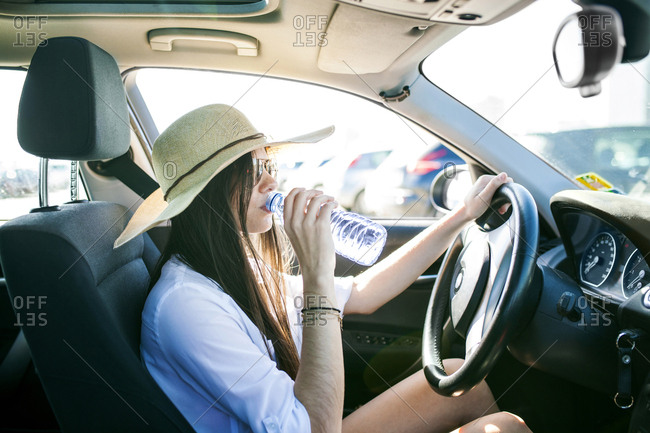 Side view of young woman drinking water while sitting in car