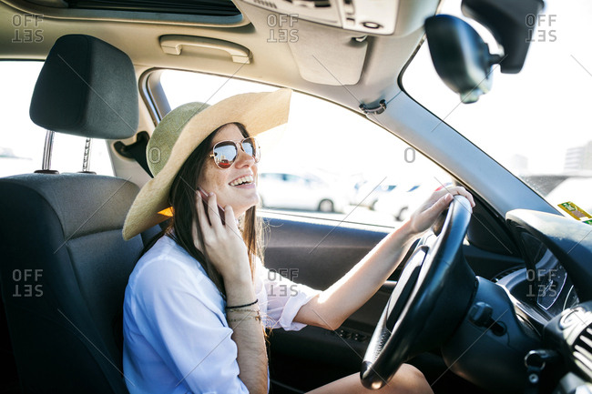 Side view of happy young woman talking on phone while sitting in car