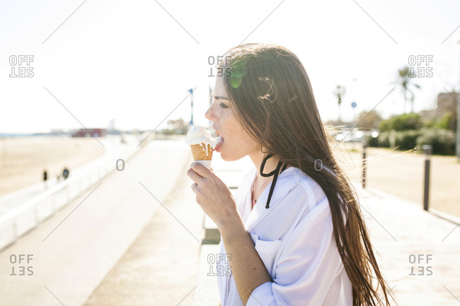 Side view of young woman licking ice cream while standing by beach against clear sky