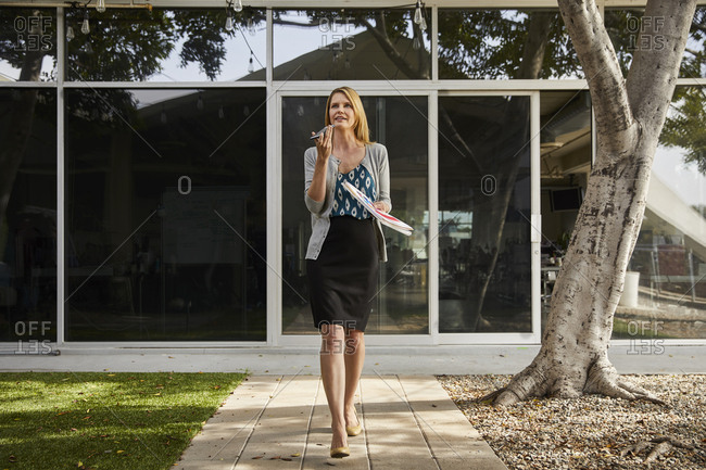 Full length of businesswoman talking through smartphone while walking outside office