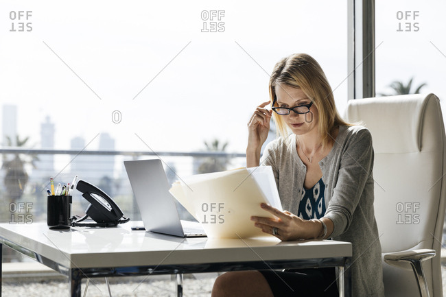 Confident businesswoman reading documents while sitting at desk in office
