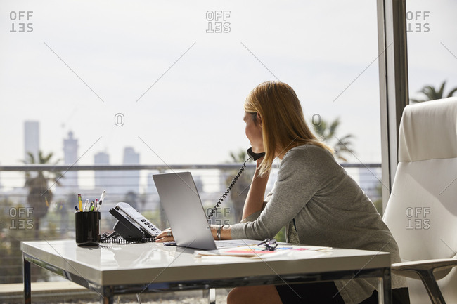 Side view of businesswoman using telephone at desk by window in office