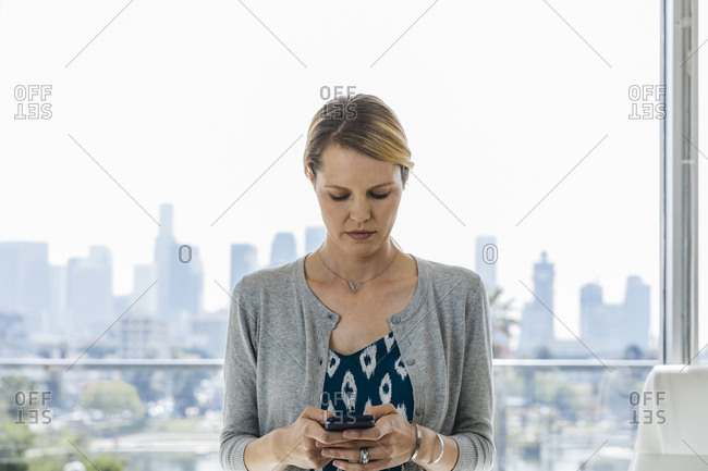 Businesswoman using smartphone while standing against window in brightly lit office