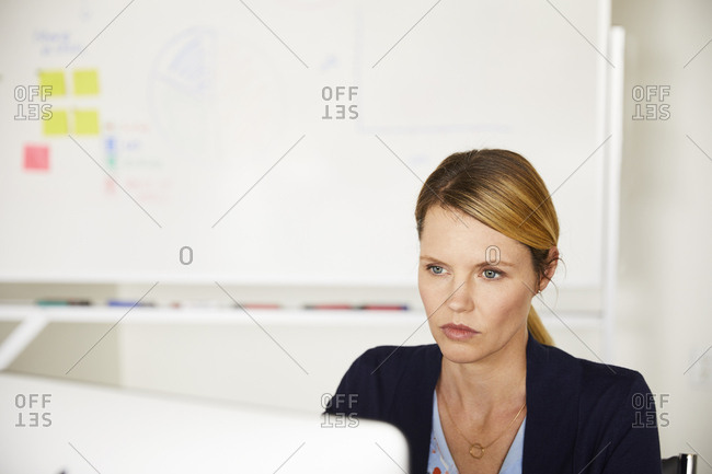 Confident mid adult businesswoman using computer in brightly lit office