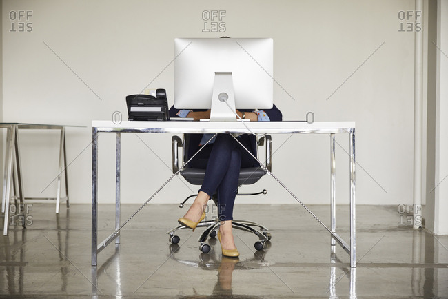 Low section of businesswoman sitting at computer desk in office