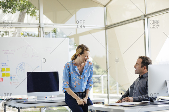 Cheerful businesswoman discussing with male colleague in brightly lit office